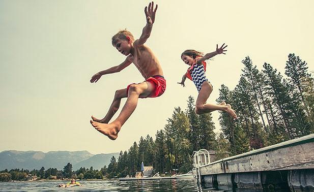 Barn hoppar från brygga
